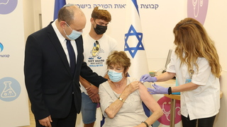 Prime Minister Naftali Bennett accompanies his mother Myrna as she receives the third dose of the coronavirus vaccine