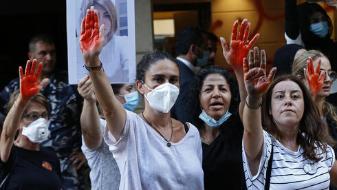 Tracy Naggear, center left, the mother of 3-year-old Alexandra, who was killed in last year's massive blast at Beirut's seaport, and relatives of others who were killed, raise their red-painted hands representing blood, during a protest outside the home of caretaker Interior Minister Mohamed Fehmi, in Beirut, Lebanon