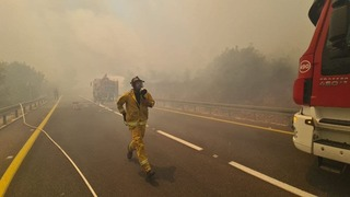 A firefighter on Highway 1, the main route leading from the center of the country to Jerusalem, closed due to fire