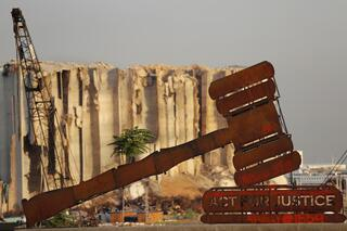 A justice symbol monument is seen in front of towering grain silos that were gutted in the massive August 2020 explosion at the port of Beirut