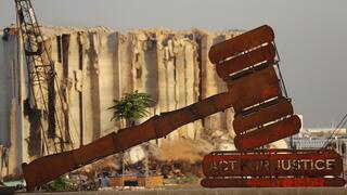 A justice symbol monument is seen in front of towering grain silos that were gutted in the massive August 2020 explosion at the port that claimed the lives of more than 200 people, in Beirut, Lebanon