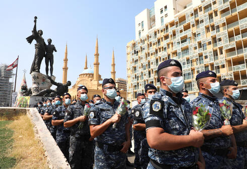 Members of internal security forces march and hold flowers as they mark one-year anniversary of Beirut port explosion