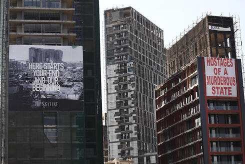 Banners hang on buildings that were damaged during the last year seaport explosion during a commemoration of the first year blast anniversary in Beirut