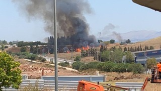Fire burns at the apparent site of a rocket strike near Kiryat Shmona, close to the border with Lebanon, on Wednesday