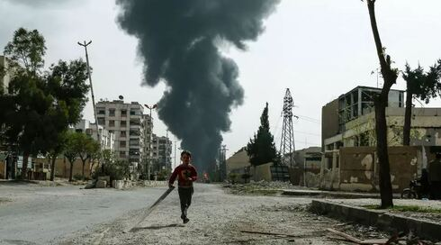 A child runs along a street in front of clouds of smoke billowing following a reported air strike on Douma, the main town of Syria's rebel enclave of Eastern Ghouta on March 20, 2018.
