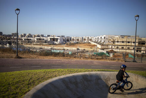 A boy rides his bicycles in a public park overlooking a construction site in Sderot, Israel, Wednesday, July 21, 2021