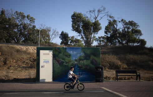 A boy rides his bicycles past a painted concrete bomb shelter placed in a public park in Sderot, Israel, July 21, 2021