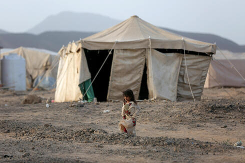 A girl walks by a tent in a camp for internally displaced people in Ma'rib province, Yemen in April