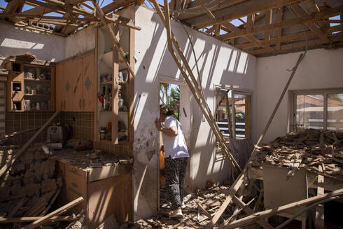 A woman surveys her damaged home after it was struck by a rocket fired from the Gaza Strip, in Sderot, May 15, 2021
