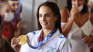 Linoy Ashram shows her gold medal to fans upon her return to Israel on Wednesday