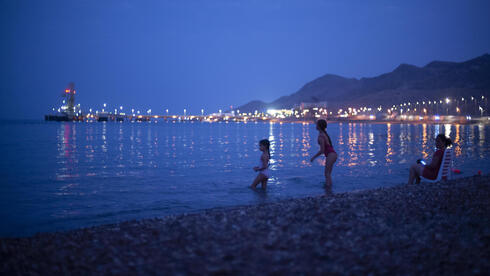 Kids play in the Red Sea beachfront backdropped by the Europe-Asia Pipeline Company (EAPC) oil jetty in Israel's southern city of Eilat, Thursday, Aug, 5. 2021