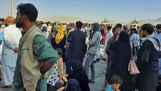 Afghans gather at Kabul airport hoping to board flights out of the Afghanistan earlier this month