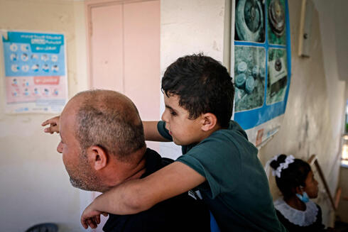 Palestinian pupil Mohammed Shaban's father Hani carries the young boy to class, at school in beit Lahia in the northern Gaza Strip, on August 17, 2021