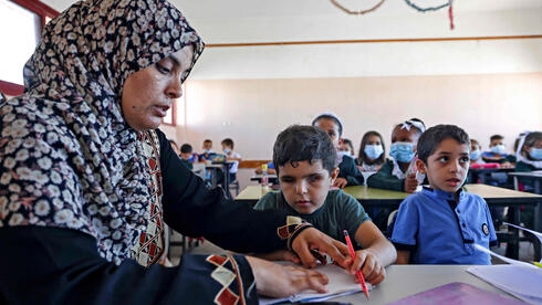 Palestinian pupil Mohammed Shaban is helped by his mother Somaya during class in beit Lahia, in the northern Gaza Strip