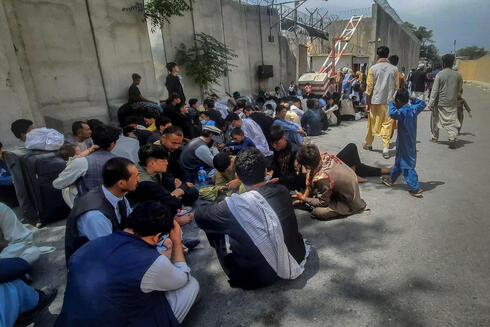 Afghan people sit outside the French embassy in Kabul on August 17, 2021 waiting to leave Afghanistan