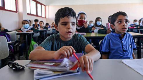 Palestinian pupil Mohammed Shaban (L) sits alongside classmates at school in beit Lahia, in the northern Gaza Strip