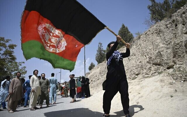 An Afghan waves the national flag in Kabul