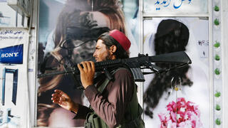 Taliban fighter walks past a poster of a woman that has been defaced
