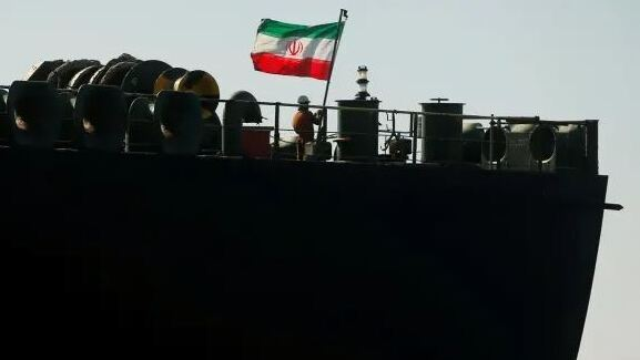 A crew member raises the Iranian flag on Iranian oil tanker Adrian Darya 1, previously named Grace 1, as it sits anchored after the Supreme Court of the British territory lifted its detention order, in the Strait of Gibraltar