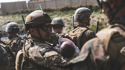 A U.S. serviceman at the Kabul airport holds an Afghan baby before his extraction from Afghanistan on Saturday
