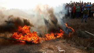 Palestinians riot near the perimeter fence on August 24, 2021