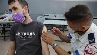A man receives his booster shot against COVID in Holon last August