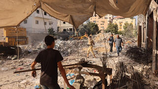 Palestinian workers straighten steel bars extracted from the ruins of buildings destroyed in the last round of Israeli-Hamas fighting, in Gaza City, on August 25, 2021