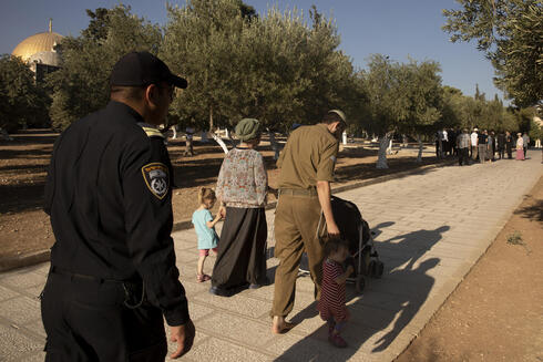 An Israeli police officer escorts a Jewish couple strolling the grounds of the Temple Mount in the Old City of Jerusalem, Tuesday, Aug. 3, 2021