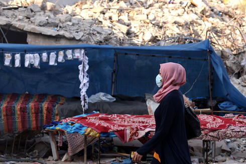 A Palestinian woman wearing a face mask walks past the ruins of buildings destroyed in the lasted round of Israeli-Hamas fighting, in Gaza City, on August 25, 2021