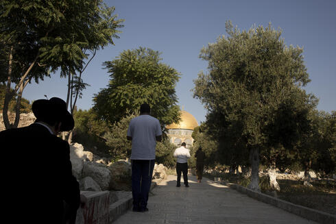 Religious Jews face the Temple Mount in the Old City of Jerusalem, Monday, Aug. 2, 2021