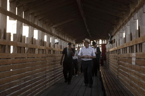 Religious Jews walk on a rickety wooden bridge from the Western Wall to pray at the Temple Mount in the Old City of Jerusalem, Tuesday, Aug. 3, 2021