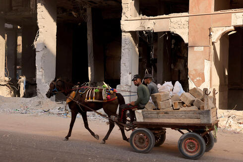 Palestinians ride a horse cart carrying rubble past the ruins of buildings destroyed in the last round of Israeli-Hamas fighting, in Gaza City, on August 25, 2021