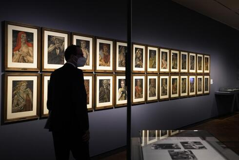 A women takes a photo of the artwork 'Demons of the Hour' by artist Werner Peiner at the exhibition