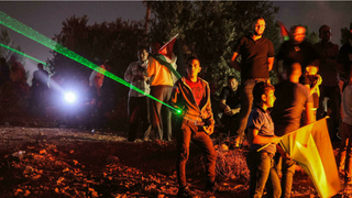 Palestinian rioters in Beita use laser pointers during a demonstration against the Israeli settler outpost of Eviatar on July 1, 2021