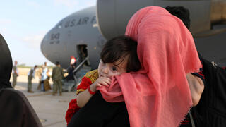 Afghan woman and her child arrive at Kuwait airport after being airlifted out of Afghanistan after Taliban takeover, August 28, 2021
