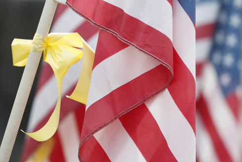 An American flag and yellow ribbon sit outside the house of Darren Hoover, whose son, Staff Sgt. Taylor Hoover was killed in Afghanistan