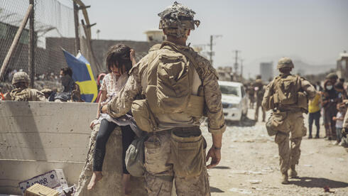 A marine cares for young child awaiting processing at an evacuation control checkpoint during an evacuation at Kabul airport
