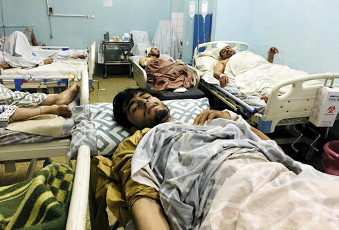 Wounded Afghans lie on a bed at a hospital after a deadly explosions outside the airport in Kabul