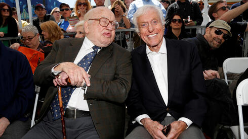 Actor Dick Van Dyke smiles as Ed Asner sticks his tongue out to make a face for the camera