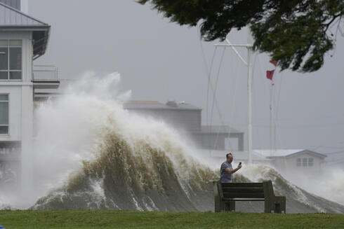 A man takes pictures of high waves along the shore of Lake Pontchartrain as Hurricane Ida nears
