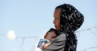 An Afghan woman and her month-old son are seen outside the new temporary camp for migrants and refugees, on the island of Lesbos, Greece