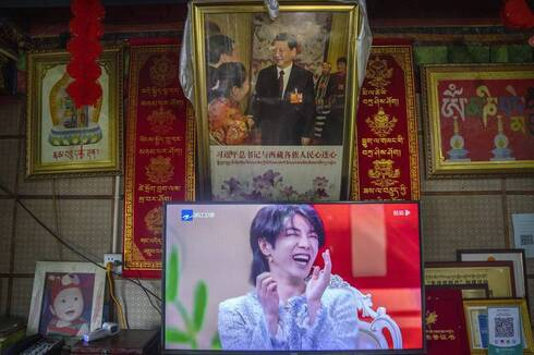 a television shows a broadcast of a Chinese talk show program as it sits beneath a photo of Chinese President Xi Jinping in a home converted into a tourist homestay in Zhaxigang village near Nyingchi in western China's Tibet Autonomous Region