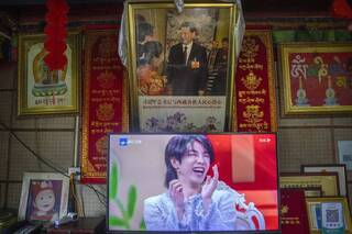 A television shows a broadcast of a Chinese talk show program as it sits beneath a photo of President Xi Jinping in a home converted into a tourist homestay in Zhaxigang village near Nyingchi in western China's Tibet Autonomous Region