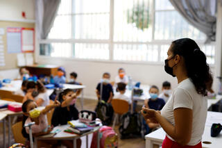 Students and teacher wearing face masks in the classroom at Tel Aviv's Arazim elementary school