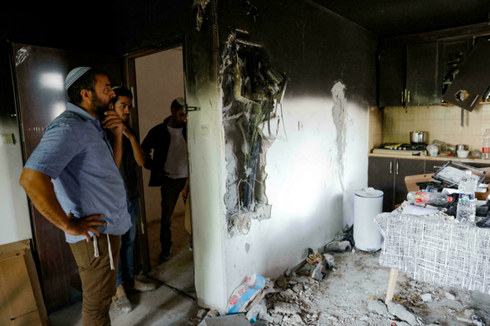Israelis stand in a home that was damaged by fire during the intra-communal violence in Lod