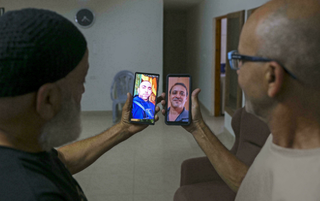 Malek Hassuna, left, holds up his phone with a picture of his late son Mussa, and Effi Yehoshua shows a photo of his late brother Yigal