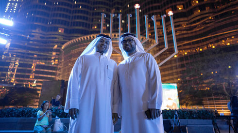 Two local residents of the UAE stand in front of a Hanukah Menorah in Dubai last December