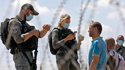 Police forces question Palestinian workers near the border crossing into the northern West Bank on Tuesday