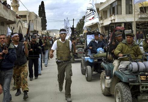 Zakaria Zubeidi, center, then local leader of the Al Aqsa Martyrs Brigades and other militants march in the West Bank town of Jenin during a rally to mark the third anniversary of the assault by the Israeli army on the Jenin refugee camp