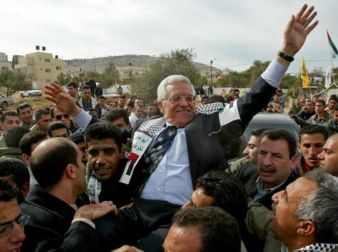 then Interim Palestinian leader Mahmoud Abbas, and front-runner in the upcoming presidential elections, is carried by the Al Aqsa Martyrs' Brigades leader in West Bank, Zakaria Zubeidi, center left, during a campaign visit to the Jenin refugee camp